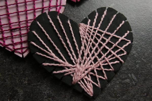 black cardboard heart with pink string