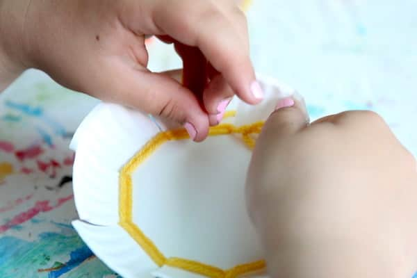 child weaving on paper plate