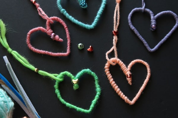 close up heart ornaments made with pipe cleaners wrapped with yarn