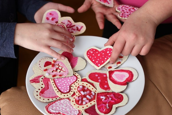 Kids putting heart shaped cardboard Valentines cookies on plate