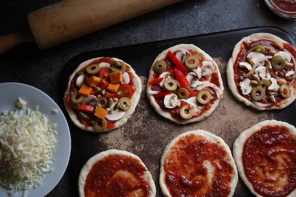 6 homemade mini pizzas on baking stone