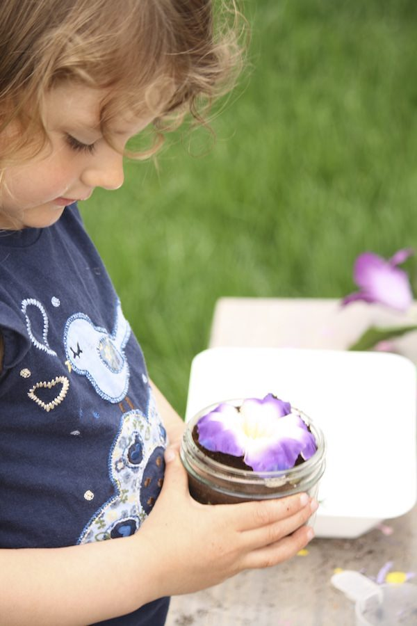 child holding artificial flower in glass jar of coffee grounds
