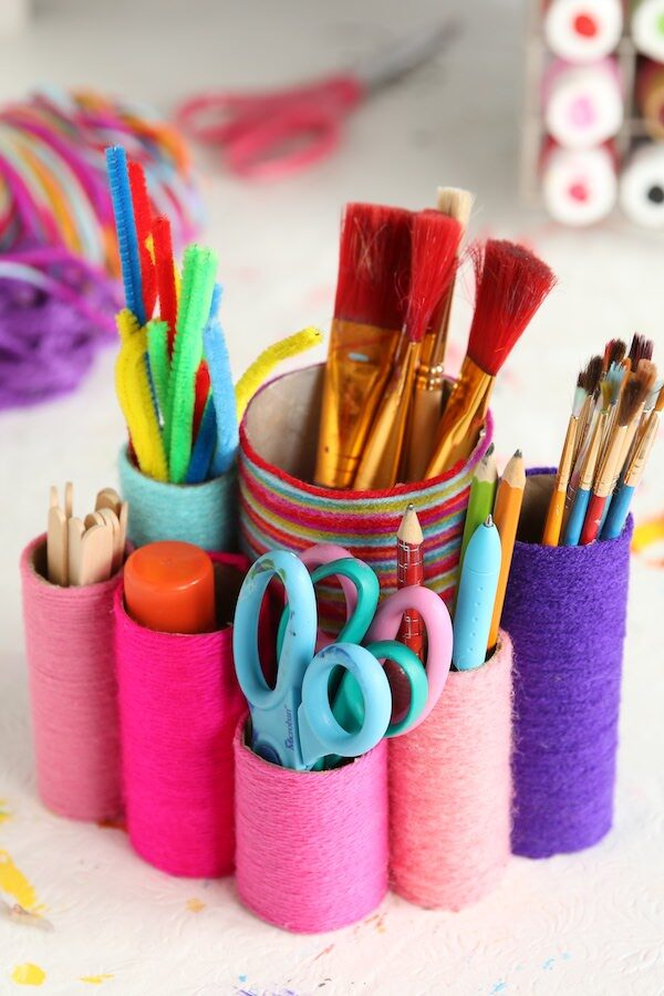 toilet roll desk organizer holding pens, pencils, scissors, paintbrushes, craft sticks and pipe cleaners