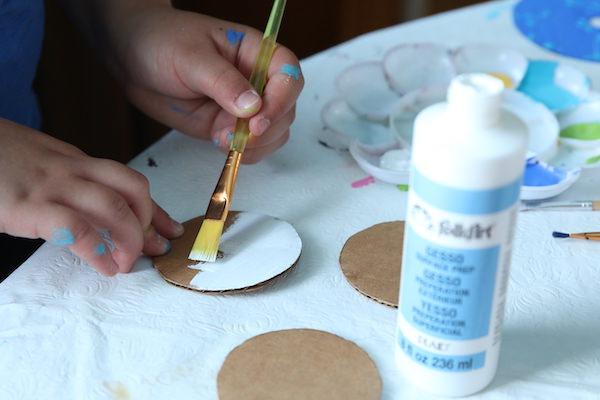 kid painting cardboard circle white