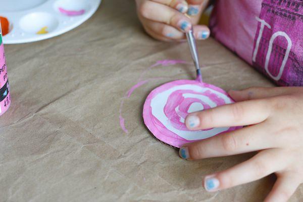 kid painting pink lollipop