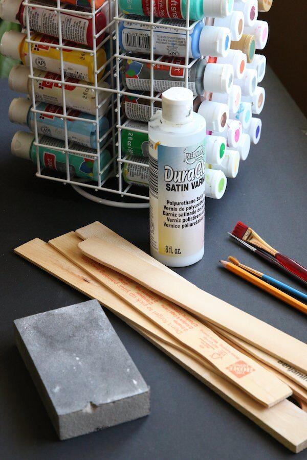 Paint sticks, paint, paint brushes, sanding block, varnish