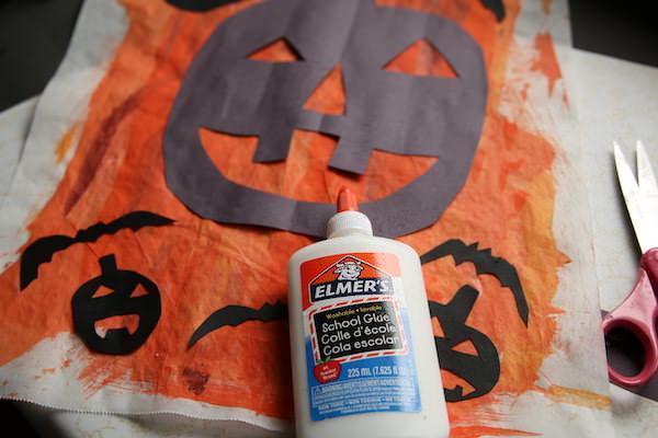 glue bottle, pumpkin and bat shapes on orange painted parchment paper