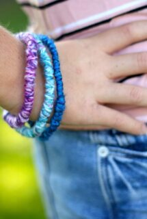 teen wearing yarn wrapped pipe cleaner bracelets, hand on hip