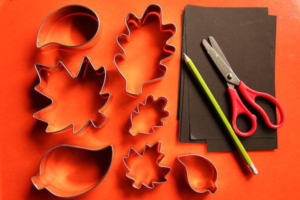 leaf cookie cutters, black paper, pencil, scissors on orange tray