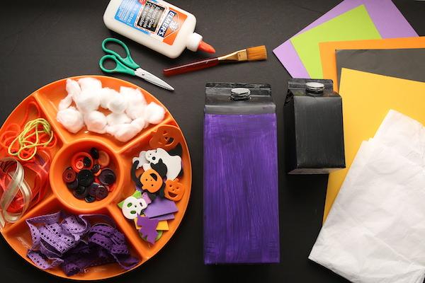 painted milk cartons, orange tray of buttons, halloween foam shapes, yarn, cotton balls