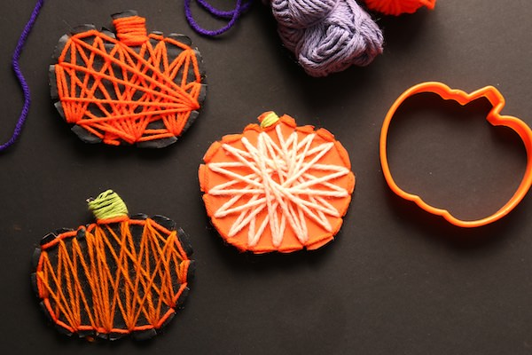 3 yarn wrapped pumpkins, balls of yarn and pumpkin cookie cutter