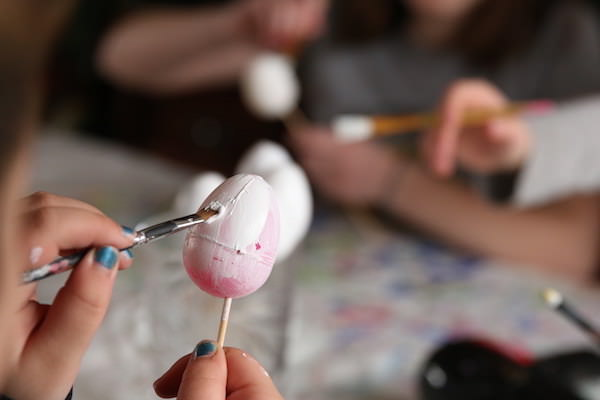 Kid priming plastic egg with Gesso