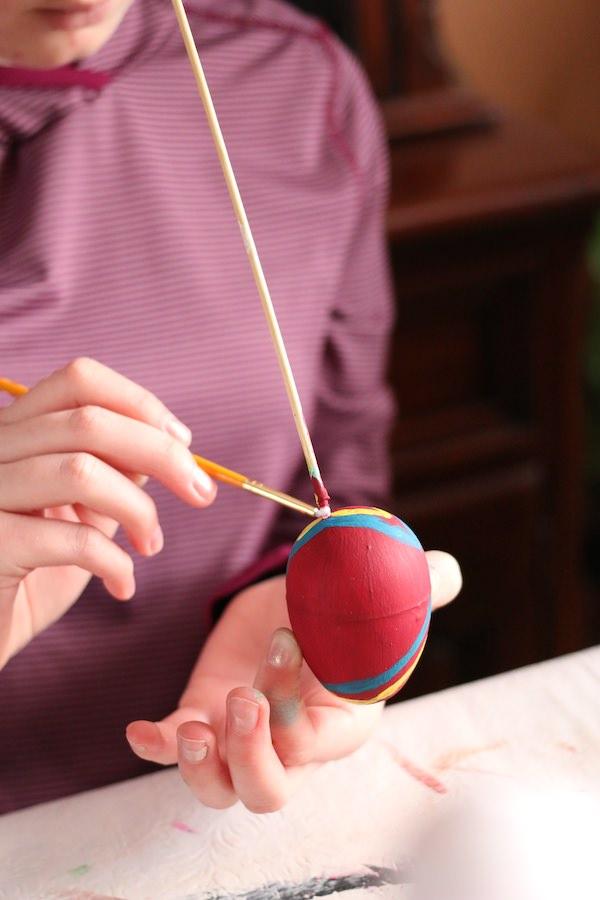 child painting plastic easter egg