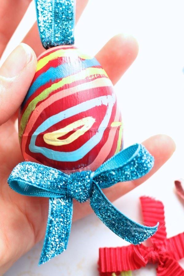hand holding plastic egg painted like European Easter Egg