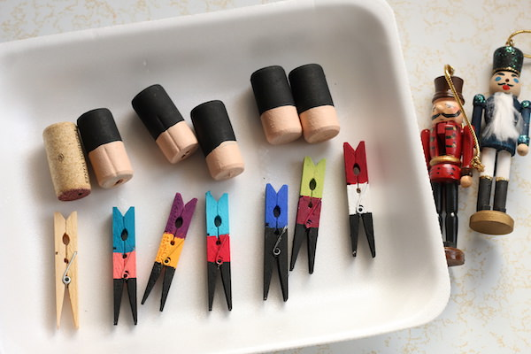 store-bought nutcracker ornaments beside tray of painted clothespins and corks