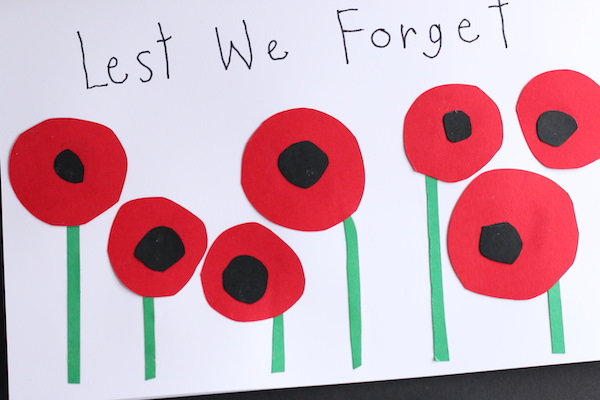 white yardstick folded horizontally 7 circle poppies with words lest we forget