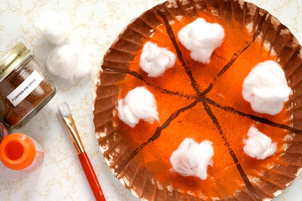 Scented pumpkin pie paper plate craft beside paint and jar of pumpkin pie spice