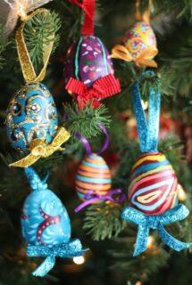 6 ornately painted plastic Easter Eggs hanging on Christmas Tree
