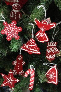 red and white painted cardboard christmas ornaments hanging on tree