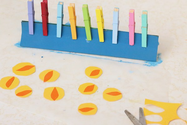 coloured clothespins on blue menorah paper flames on table