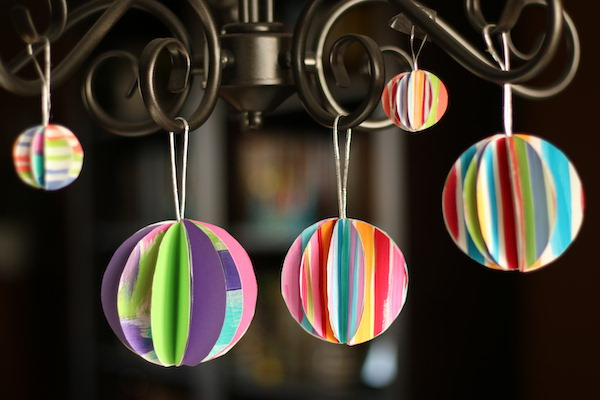 folded paper ornaments hanging from chandelier