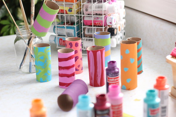painted cardboard rolls with stripes painted on