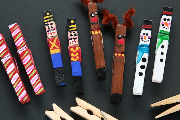 painted clothespin ornaments on black background with unpainted wooden clothespins
