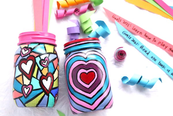 colourful painted mason jars with curled up strips of paper in them.