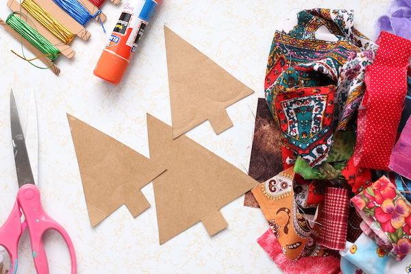 Cardboard Christmas tree cutouts, fabric scraps, scissors, glue stick