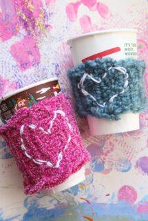 2 coffee cups with kid-made coffee sleeves, hearts stitched on front