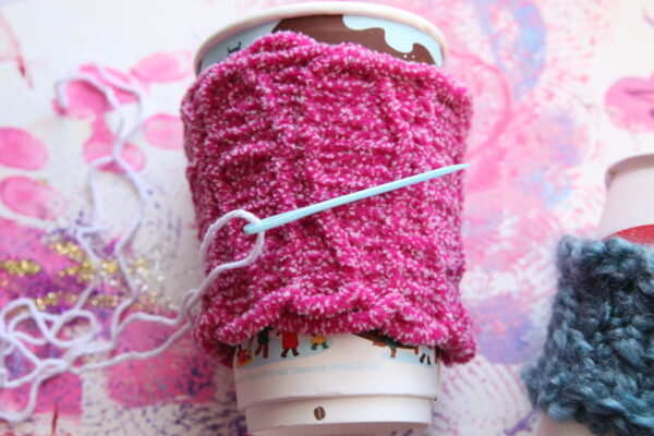 pink coffee cup sleeve with sewing needle