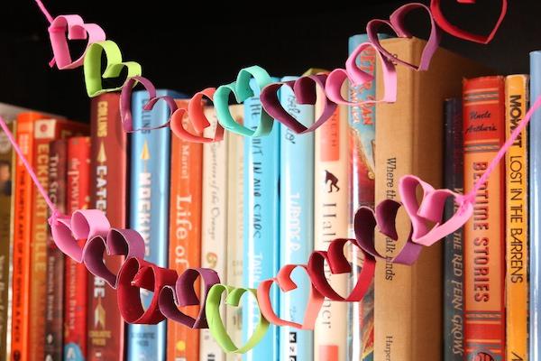 colourful tp roll heart garland strung across shelf of books