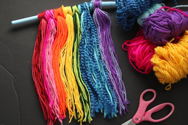 Rainbow coloured yarn tied to stick