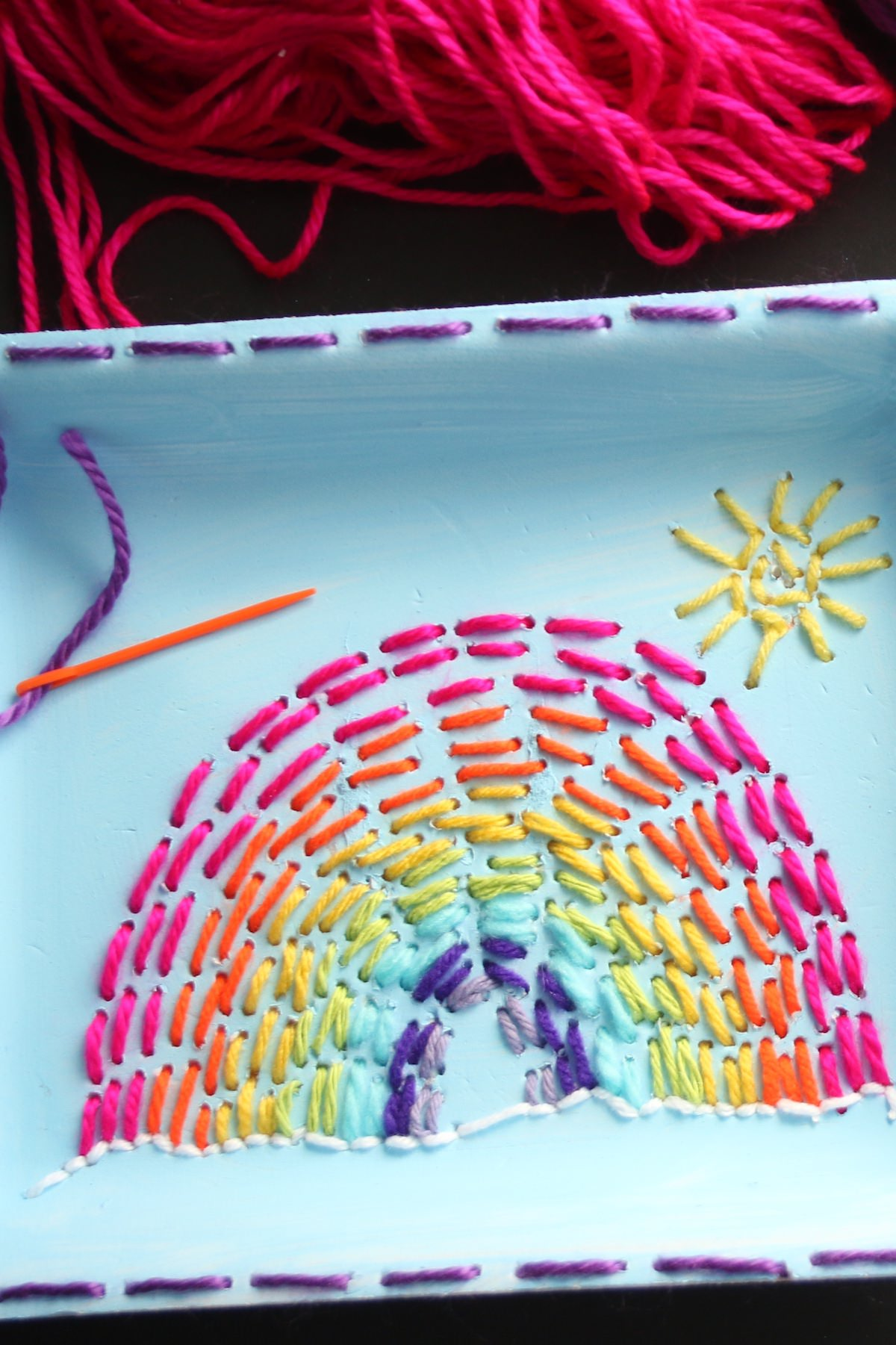 kid sewn rainbow on produce tray with small sun and orange sewing needle